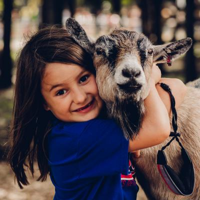 Little girl hugging a farm animal at Lucky Ladds Farms