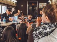Kids gather around listening to the Train Conductor reading The Night Before Christmas