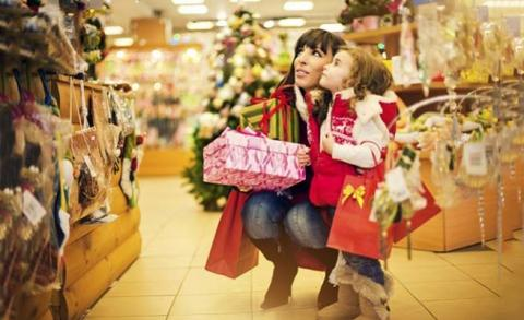 Little Girl and Her mom looking at Christmas decorations in mall